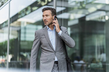 Businessman on cell phone in the city - DIGF08423
