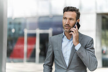 Businessman on cell phone in the city - DIGF08432