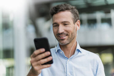 Smiling businessman with earphones and cell phone in the city - DIGF08435