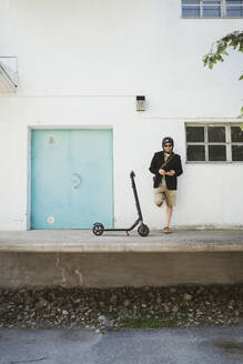 Man with Electric Scooter leaning against facade using smartphone - PSIF00315