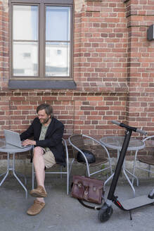 Man with Electric Scooter sitting at pavement cafe using laptop - PSIF00321