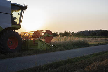 Organic farming, wheat field, harvest, combine harvester in the evening - SEBF00215