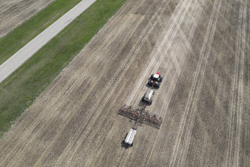 Aerial view tractor pulling agricultural equipment in sunny field - HEROF38574
