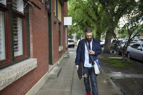 Hipster businessman with skateboard and smart phone on urban sidewalk - HEROF38901