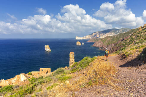 A tourist walks on a path to Laveria Lamarmora, Nebida, Iglesias, Sud Sardegna province, Sardinia, Italy, Mediterranean, Europe - RHPLF09747