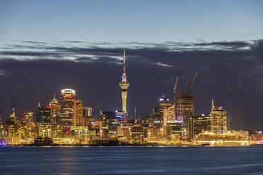 Illuminated modern buildings by sea against cloudy sky at dusk in Oceania, New Zealand - FOF10886