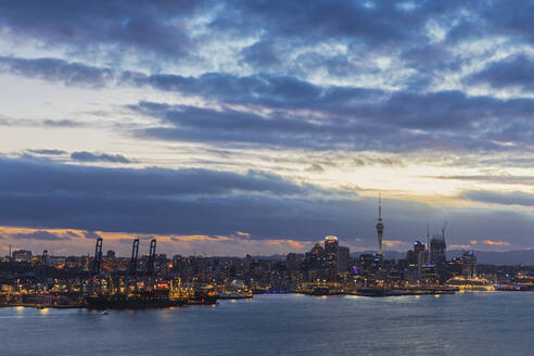 Modern buildings by sea against cloudy sky at dusk in Auckland, New Zealand - FOF10889