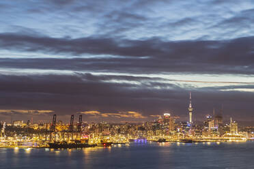 Illuminated modern buildings by sea against cloudy sky at dusk in Auckland, New Zealand - FOF10892