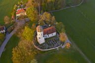 Aerial view of St. Johann Baptist church and cemetery during autumn, Holzhausen, Germany - LHF00694