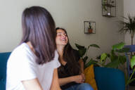 Two happy young women sitting on a couch - GIOF07045