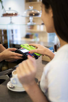 Close-up of customer paying cashless with smartphone in a cafe - GIOF07057