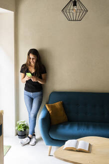 Young woman leaning against a wall using cell phone - GIOF07060