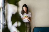 Young woman leaning against a wall using cell phone - GIOF07063