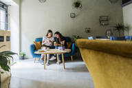 Two young female friends sitting on a couch in a cafe sharing cell phone - GIOF07069