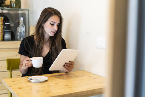 Young woman using tablet in a cafe - GIOF07078
