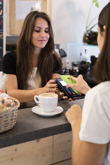 Customer paying cashless with smartphone in a cafe - GIOF07084
