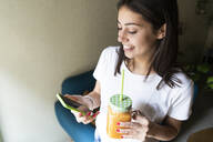 Happy young woman with a smoothie using cell phone in a cafe - GIOF07099