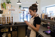 Young woman using cell phone behind the counter in a cafe - GIOF07102