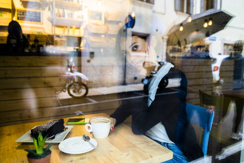 Portrait of a young woman in a cafe behind the windowpane - GIOF07108
