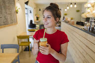 Portrait of a young woman with a smoothie in a cafe - GIOF07123