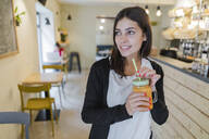 Portrait of a young woman with a smoothie in a cafe - GIOF07126