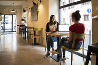Two young women with laptop in a cafe - GIOF07132