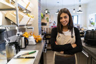 Portrait of confident young woman behind the counter in a cafe - GIOF07135