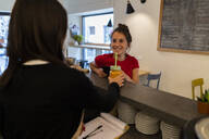 Smiling young woman at the counter in a cafe - GIOF07138