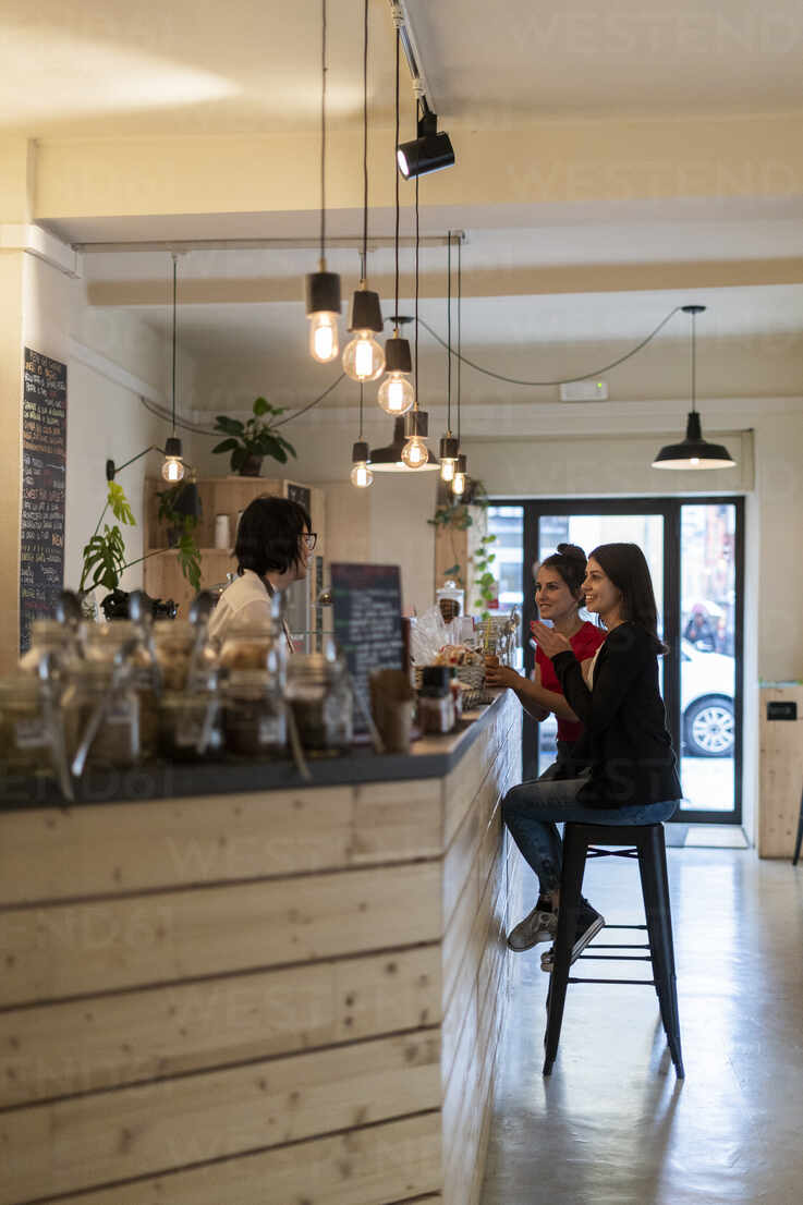 Two young female friends in a cafe talking with barista - GIOF07141 - Giorgio Fochesato/Westend61