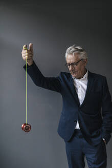 Senior businessman playing with yoyo - GUSF02548
