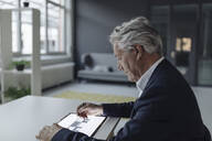 Senior businessman using tablet with architectural plan - GUSF02551