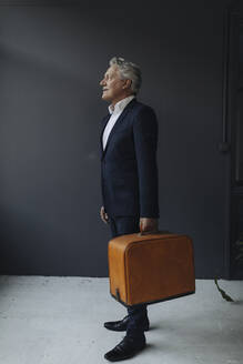 Senior businessman holding old-fashioned suitcase - GUSF02584