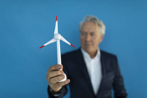 Senior businessman holding wind turbine model - GUSF02593