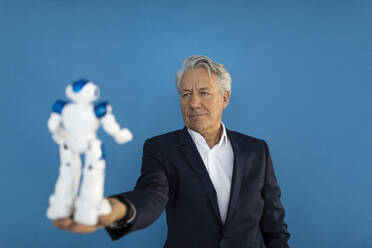 Senior businessman holding robot - GUSF02596