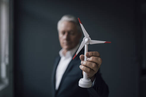 Senior businessman holding wind turbine model - GUSF02602