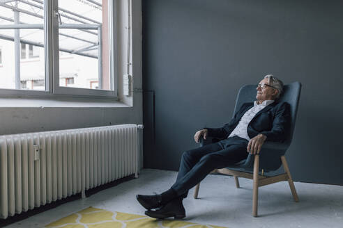 Senior businessman sitting in armchair looking out of the window - GUSF02614