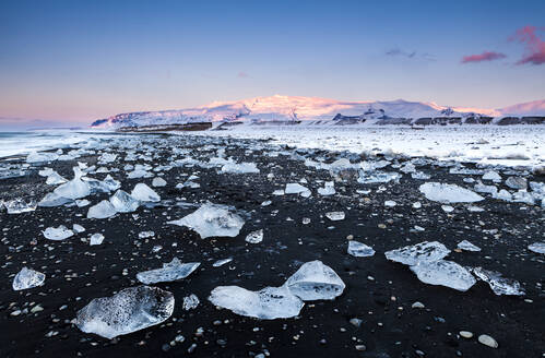 View of icebergs at black beach against sky during sunset, Jokulsarlon, Iceland - XCF00208