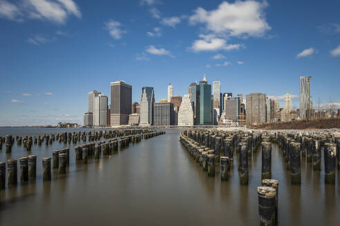 Wooden posts in East river with modern buildings in background against sky, New York City, USA - XCF00217