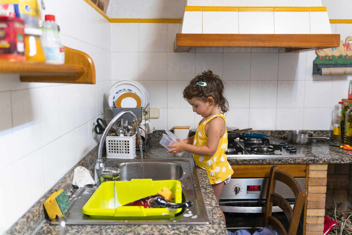 Little Girl Washing Dishes In The Kitchen At Home Stockphoto