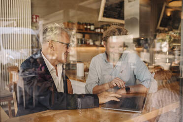 Two smiling businessmen with laptop meeting in a cafe - GUSF02619