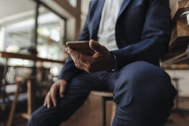 Close-up of businessman holding cell phone in a cafe - GUSF02628