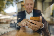 Senior businessman using cell phone in a cafe - GUSF02637
