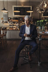 Senior businessman using cell phone in a cafe - GUSF02646