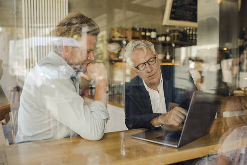 Two businessmen with laptop meeting in a cafe - GUSF02649
