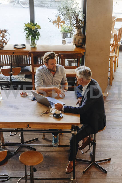 Two businessmen with laptop meeting in a cafe - GUSF02652 - Gustafsson/Westend61