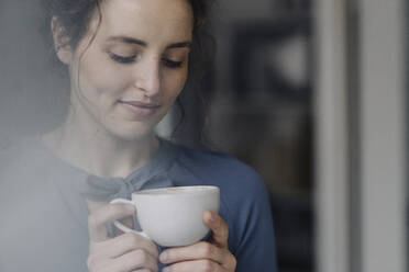 Portrait of young woman relaxing with cup of coffee - KNSF06553