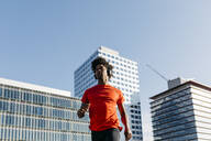 Young man jogging in the city, listening to music - JRFF03716