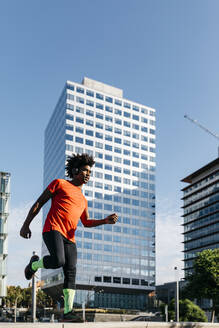 Young man jogging in the city, listening to music - JRFF03719