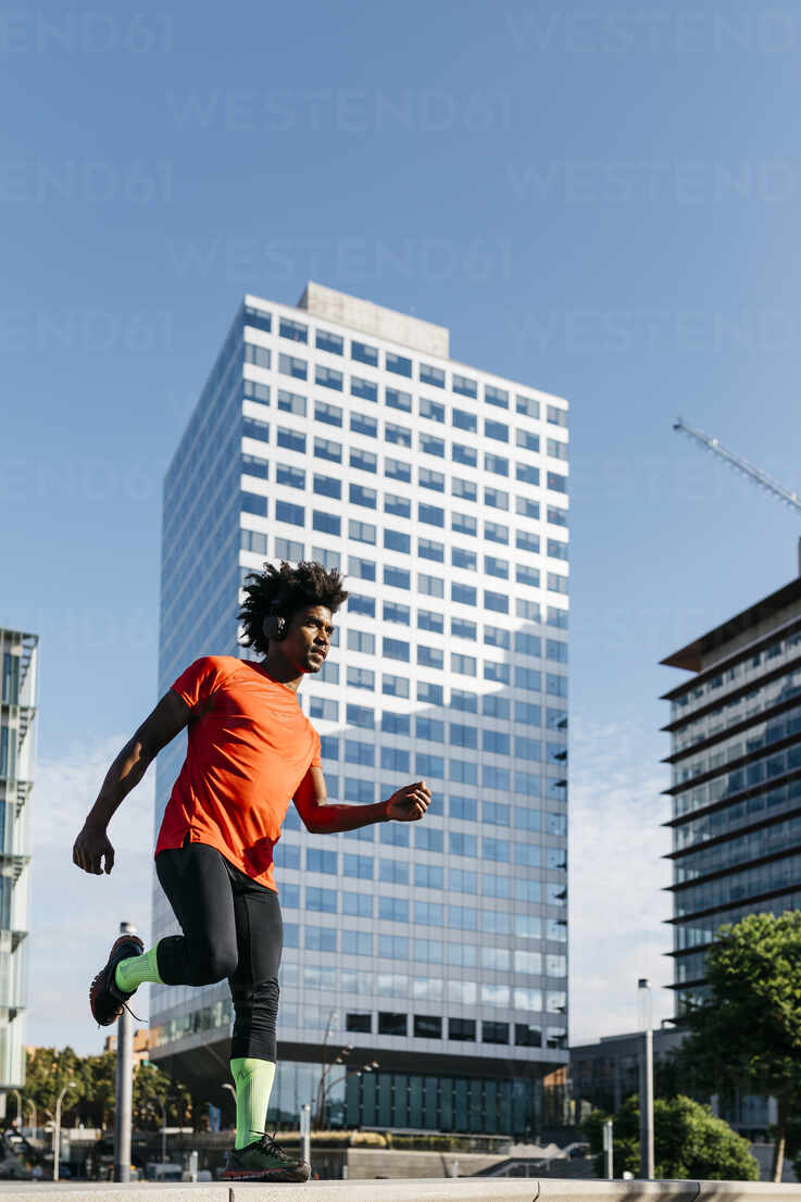 Young man jogging in the city, listening to music - JRFF03719 - Josep Rovirosa/Westend61