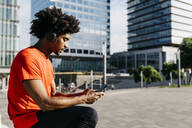 Young sportsman sitting on a bench, using smartphone and listening to music - JRFF03722